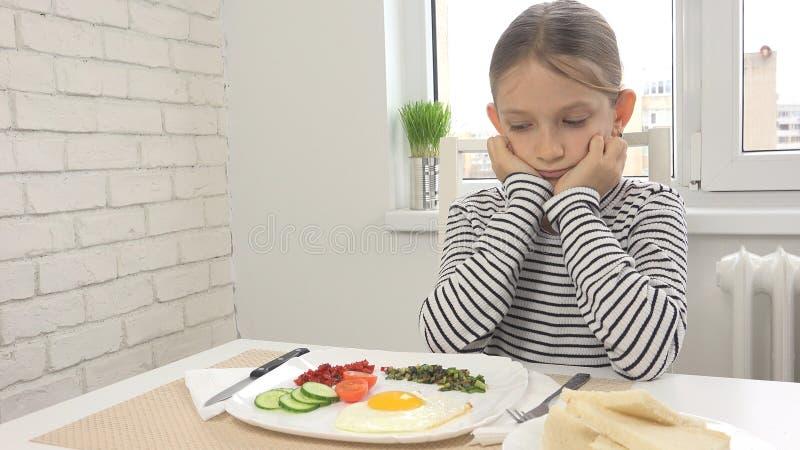 A criança doente não poderia comer o café da manhã na cozinha, olhando a refeição do alimento, nenhum apetite imagem de stock