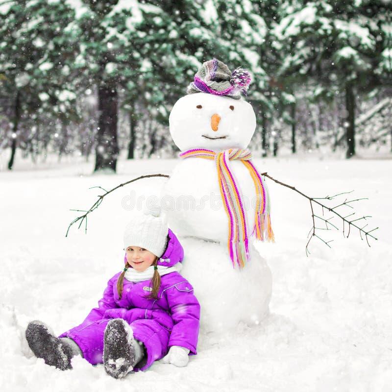 Criança e boneco de neve em um parque coberto de neve Atividades exteriores do inverno foto de stock