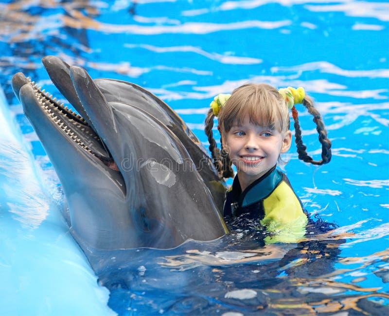 Criança e golfinho na água azul. imagem de stock