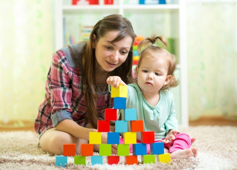 A criança e a mãe da criança constroem a torre que joga brinquedos de madeira em casa ou berçário foto de stock