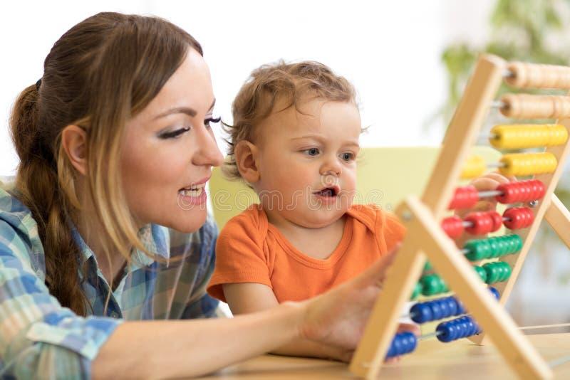 Criança e mãe que jogam com ábaco em casa foto de stock