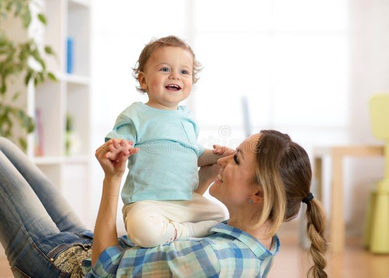 Criança e mamã de sorriso que têm um passatempo do divertimento no assoalho na sala de crianças em casa fotos de stock