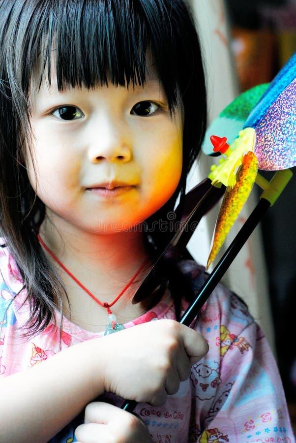 Criança e moinho de vento asiáticos foto de stock
