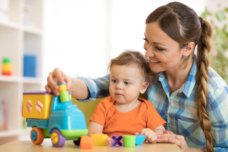 Criança e mulher que jogam com o brinquedo desenvolvente na guarda ou no jardim de infância fotos de stock