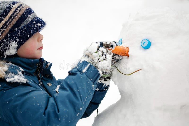 A criança e o boneco de neve fotografia de stock royalty free