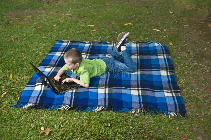 Criança e portátil no jardim fotos de stock royalty free