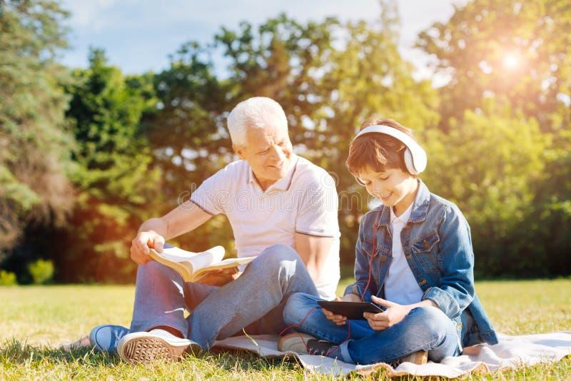 Criança e seu vovô que apreciam seus passatempos junto fotografia de stock royalty free