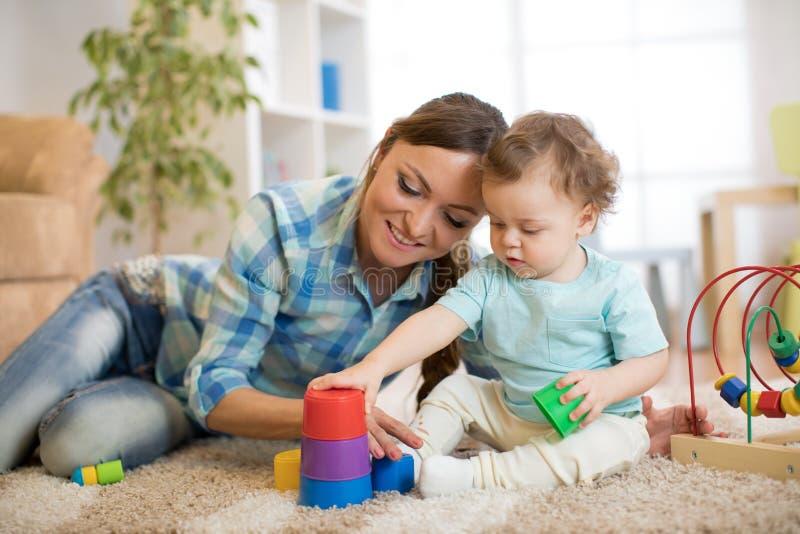 Criança e sua mãe que jogam junto com brinquedos fotos de stock royalty free