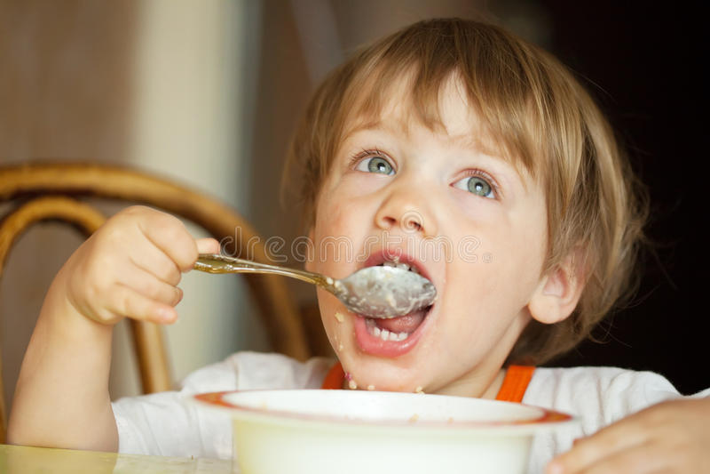 A criança ele mesmo come o cereal foto de stock