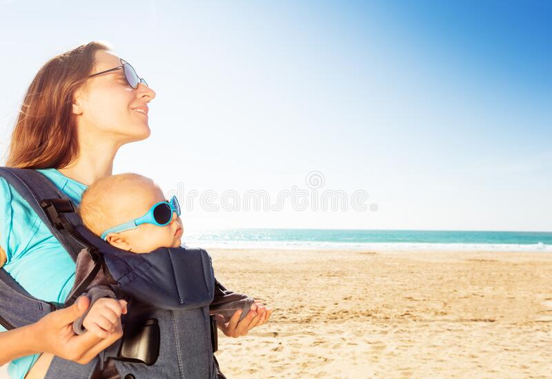Criança em carruagem de bebês com mãe na praia do mar fotografia de stock royalty free