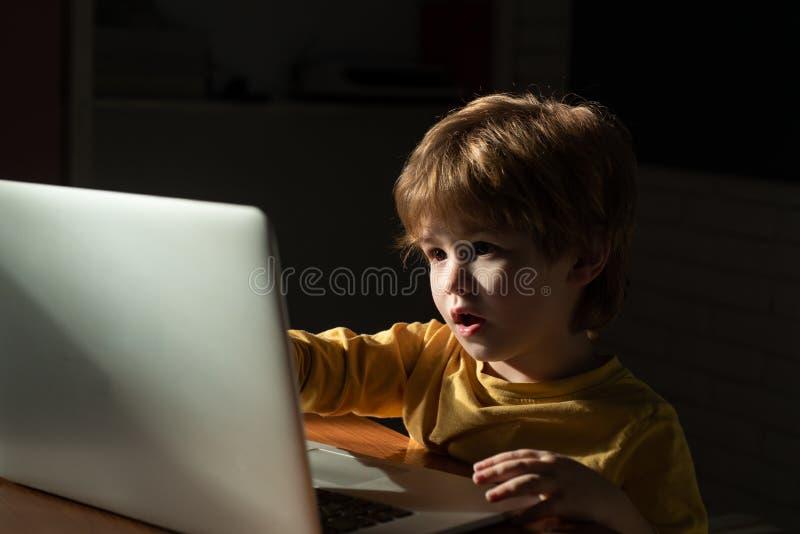 Criança em casa que usa um portátil para desenhos animados de observação Informação interessante no Internet para crianças Intern fotos de stock royalty free