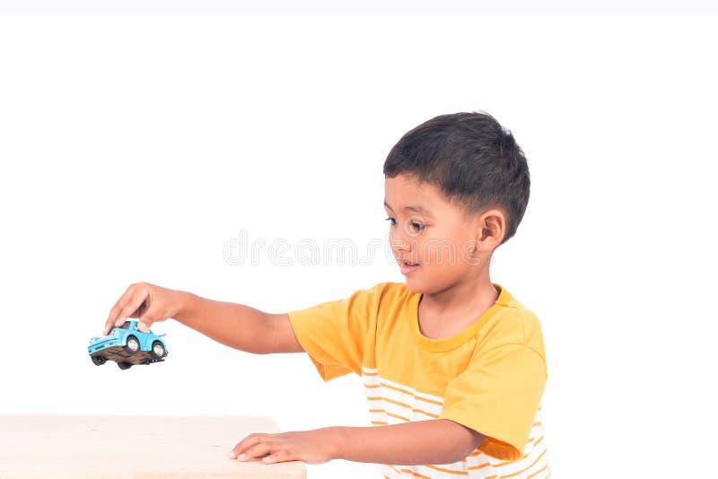 Criança em idade pré-escolar asiática pequena bonito da criança da criança do menino que joga o carro imagem de stock