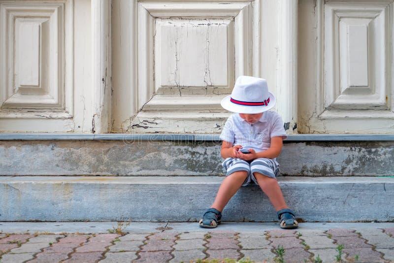 Criança em idade pré-escolar com dispositivo Menino que senta-se nas escadas com o dispositivo no regaço Crianças e tecnologias F fotografia de stock