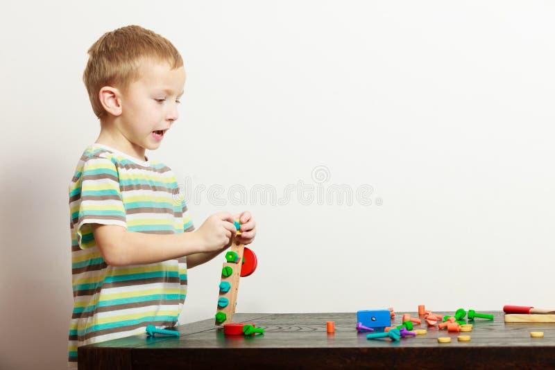 A criança em idade pré-escolar da criança da criança do menino que joga com blocos de apartamentos brinca o interior fotos de stock