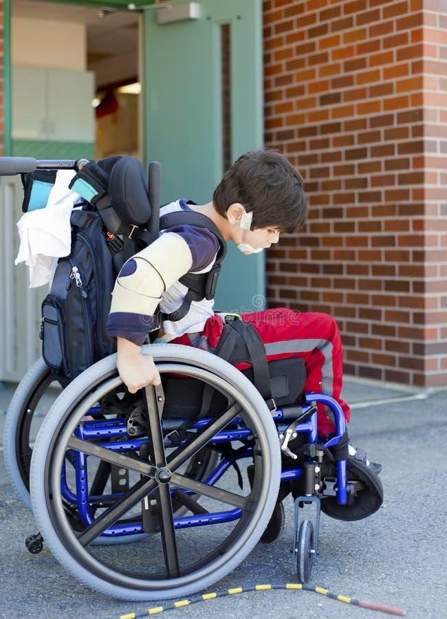 Criança em idade pré-escolar deficiente na cadeira de rodas no campo de jogos no rebaixo fotografia de stock royalty free