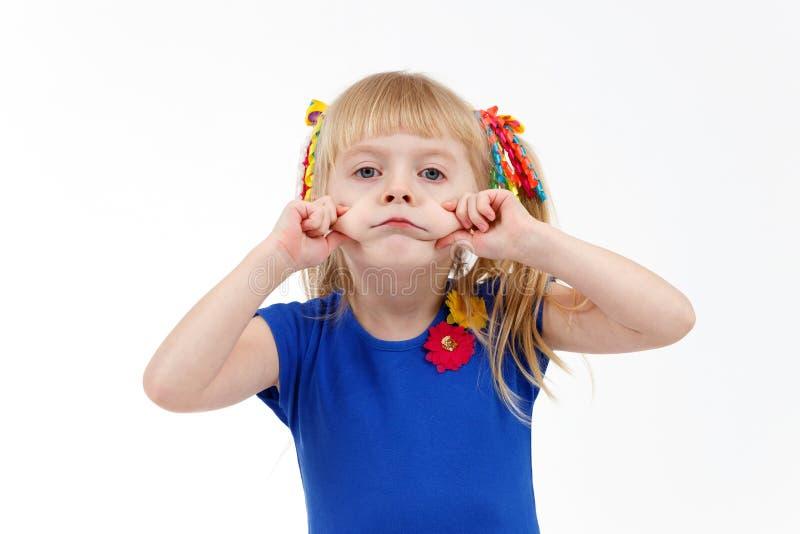 Criança em idade pré-escolar loura pequena engraçada com as duas caudas que fazem a careta triste fotos de stock