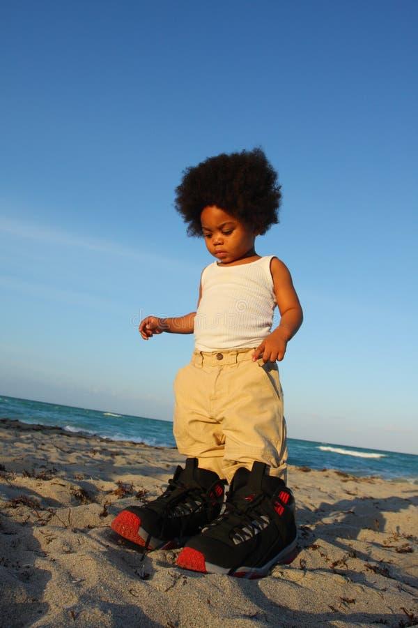 Criança em sapatas grandes foto de stock