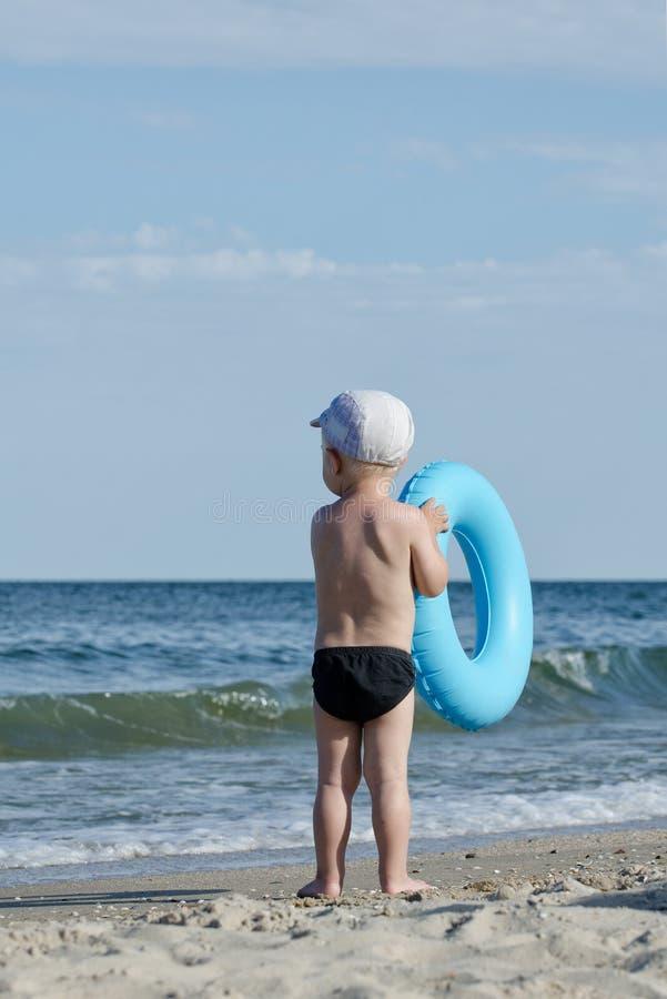A criança em troncos de natação com um círculo da natação está na costa do mar para trás foto de stock royalty free