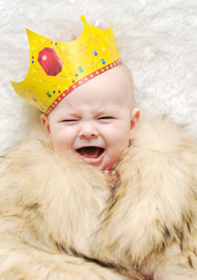 Criança em um cabo da pele e coroa em um fundo branco Baby-sitter que alimenta o bebê fotografia de stock royalty free
