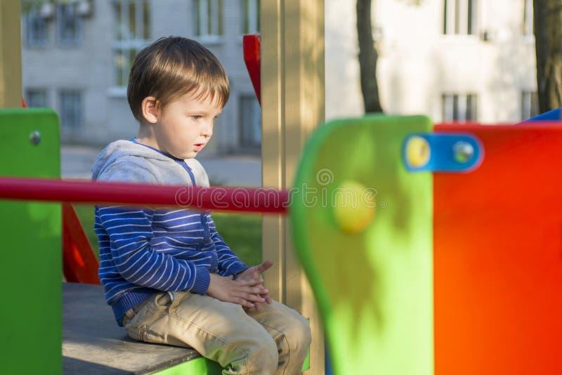 Criança em um campo de jogos Criança que joga fora no verão Jogo das crianças na jarda de escola Criança feliz no jardim de infân imagens de stock
