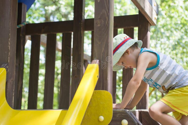 Criança em um campo de jogos Criança que joga fora no verão Jogo das crianças na jarda de escola Criança feliz no jardim de infân fotografia de stock