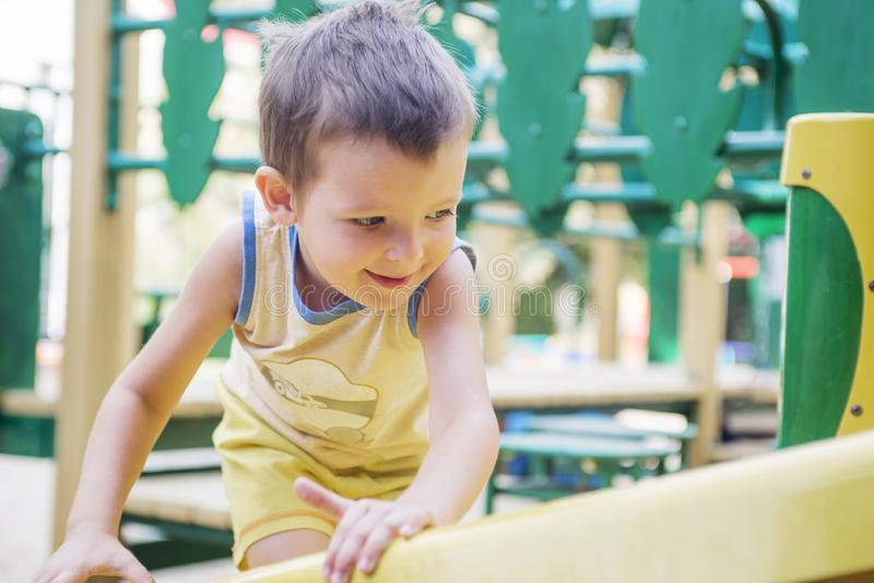 Criança em um campo de jogos Criança que joga fora no verão Jogo das crianças na jarda de escola Criança feliz no jardim de infân imagem de stock