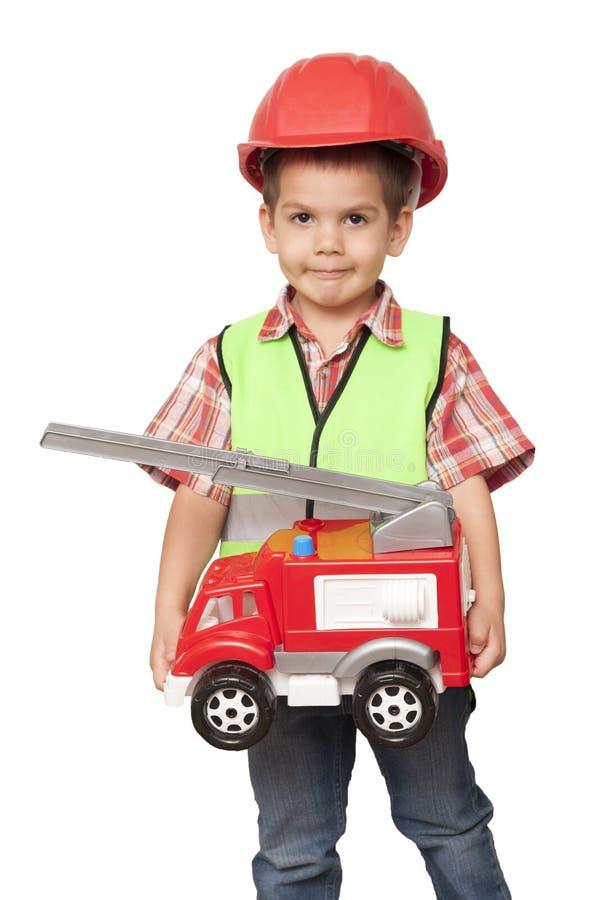 Criança em um capacete vermelho e com uma viatura de incêndio em suas mãos imagem de stock