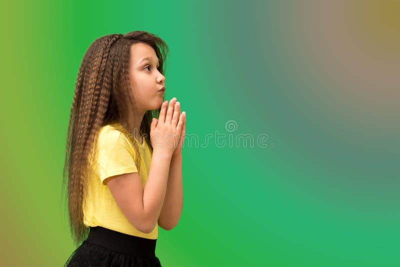 A criança em um fundo colorido dobrou suas mãos e implora-as O conceito da remissão e da oração foto de stock