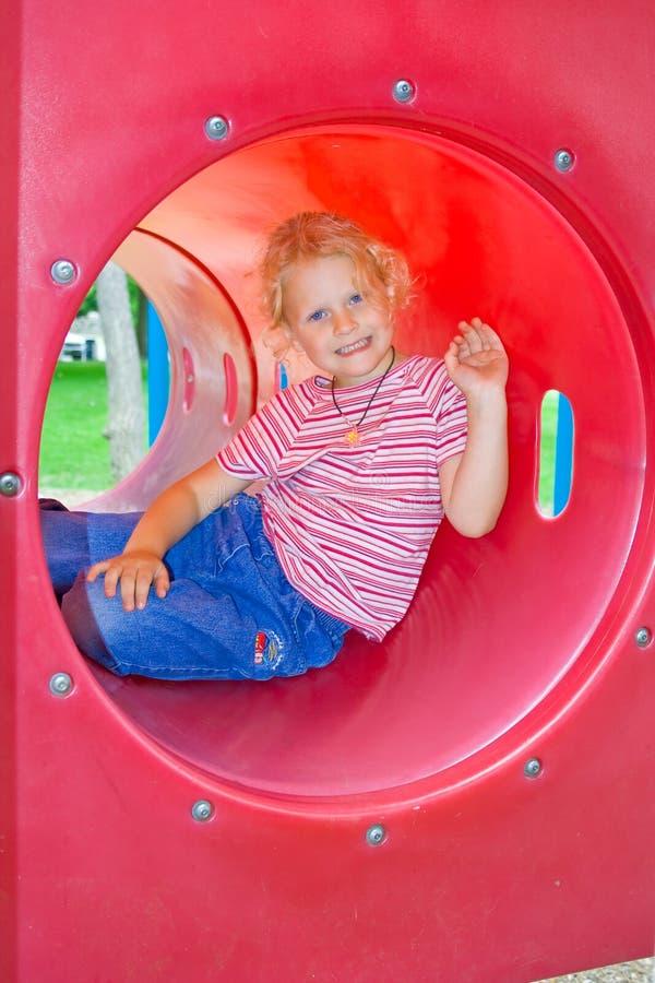 Criança em um túnel vermelho do jogo. fotografia de stock