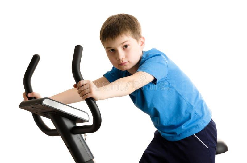 Criança em uma bicicleta de exercício imagem de stock royalty free