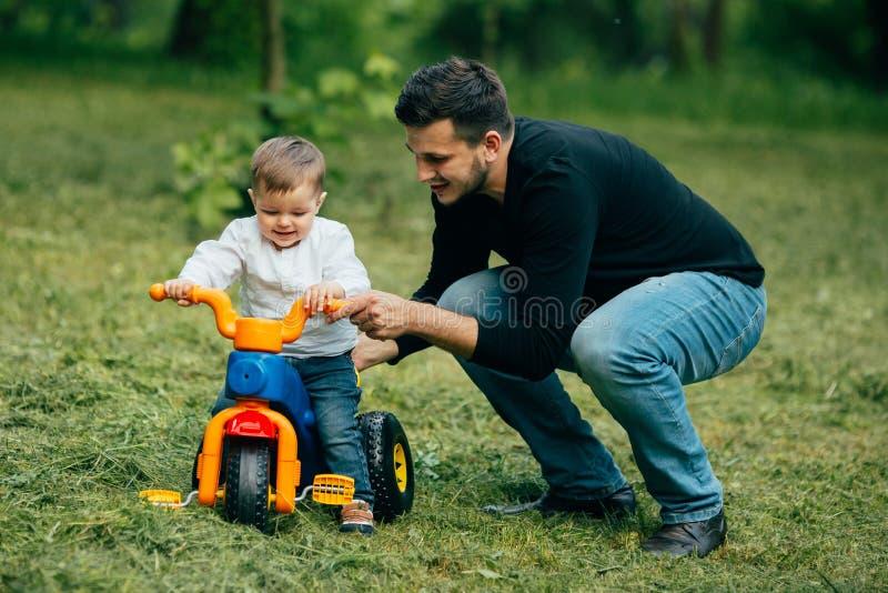 A criança em uma bicicleta obtém das primeiras lições do pai foto de stock