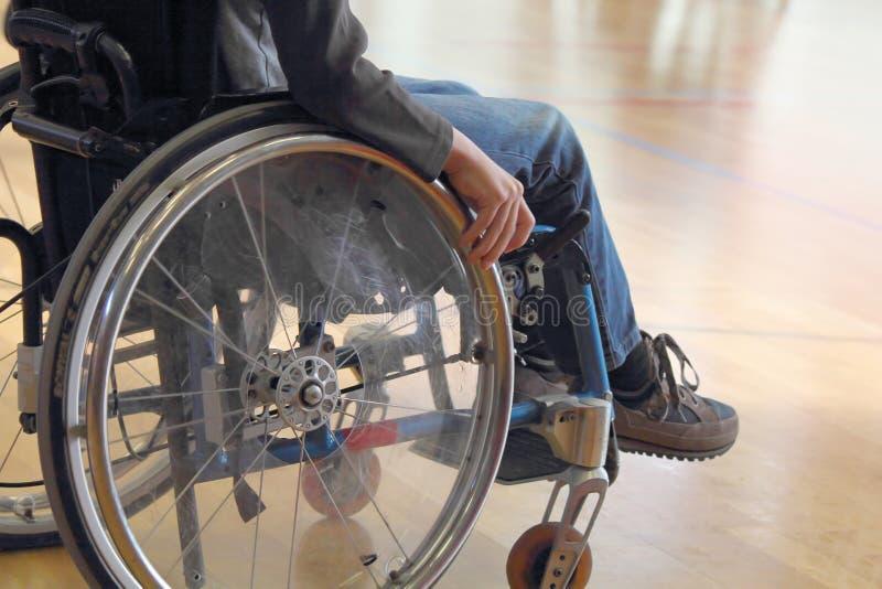 Criança em uma cadeira de rodas em um gym foto de stock