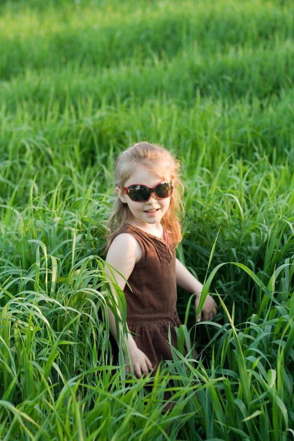 A criança em uma grama imagem de stock royalty free
