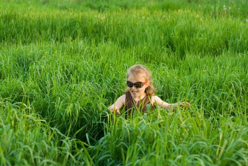 A criança em uma grama fotos de stock