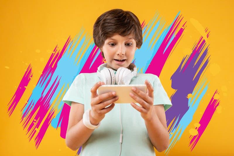 Criança emocional que sente entusiasmado ao jogar jogos de vídeo foto de stock