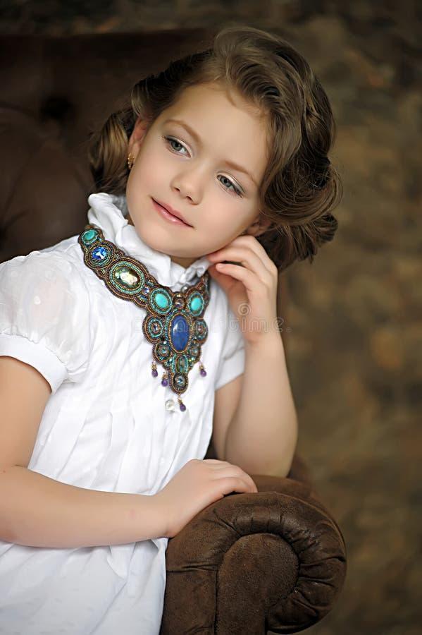 Criança encantador da menina em uma blusa branca com uma colar bonita fotografia de stock royalty free