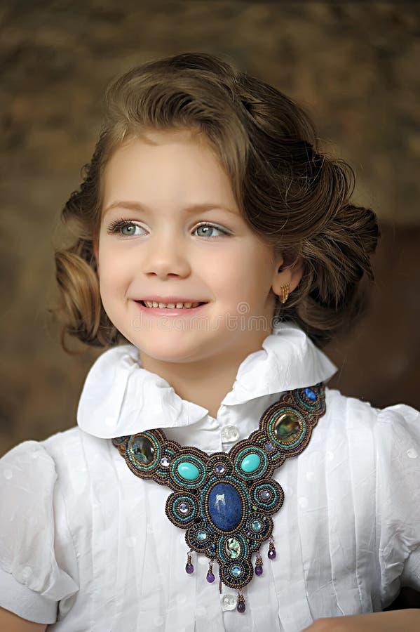 Criança encantador da menina em uma blusa branca com uma colar bonita fotografia de stock
