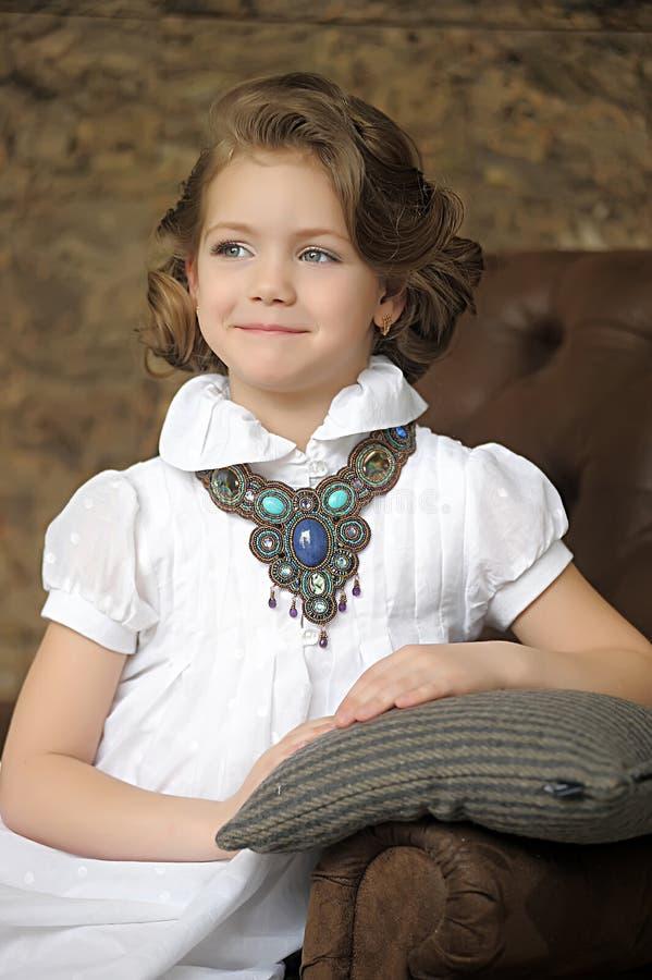 Criança encantador da menina em uma blusa branca com uma colar bonita fotos de stock