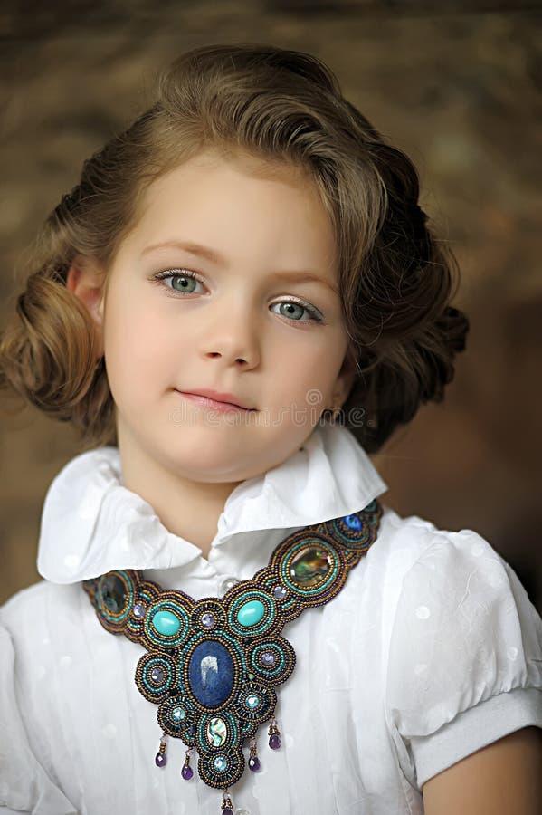 Criança encantador da menina em uma blusa branca com uma colar bonita imagens de stock royalty free