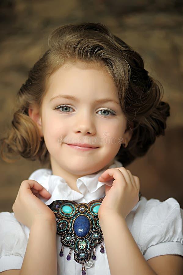 Criança encantador da menina em uma blusa branca com uma colar bonita imagem de stock royalty free