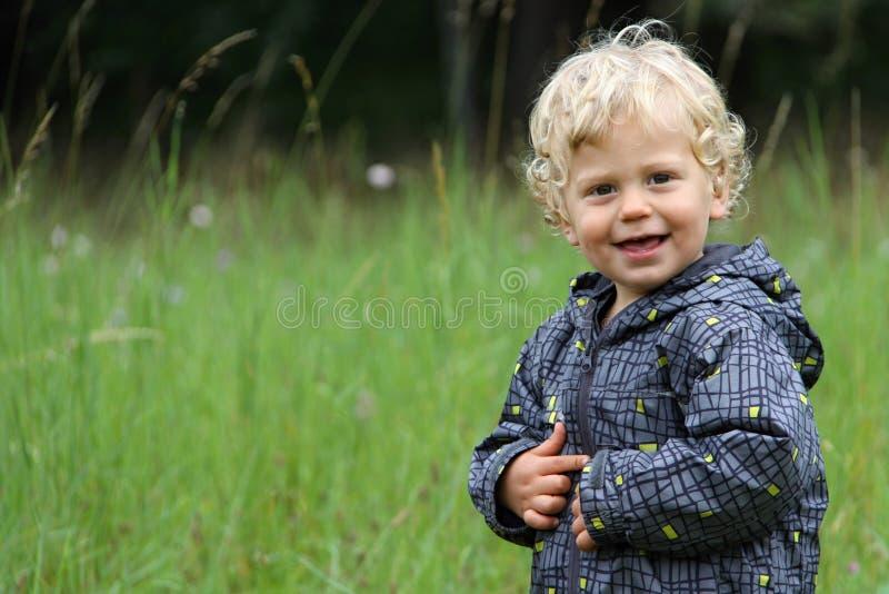 Criança encaracolado pelo prado verde no outono fotos de stock royalty free