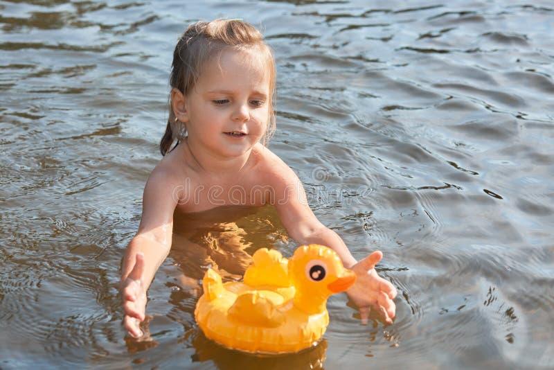 Criança energética entusiástica que nada na água apenas, apreciando o resto no rio limpo, passando férias de verão na unidade com fotos de stock