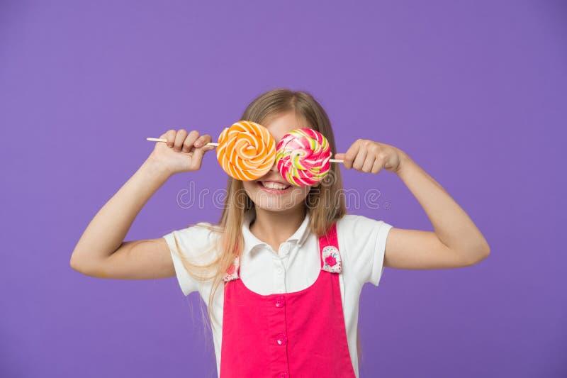 Criança engraçada com os pirulitos no fundo violeta Menina que sorri com olhos dos doces Sorriso da criança com os doces em varas imagem de stock royalty free