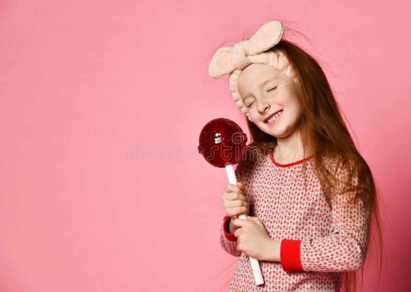 Criança engraçada com pirulito dos doces, menina feliz que come o pirulito grande do açúcar imagem de stock royalty free