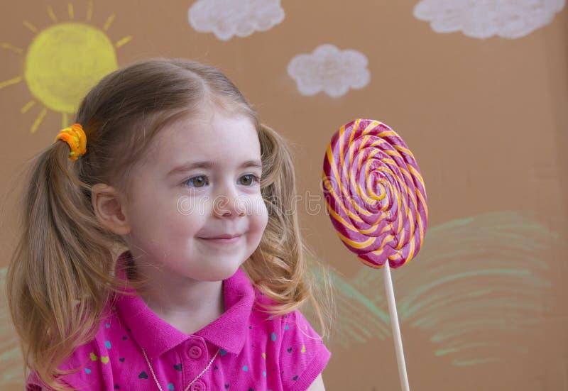 A criança engraçada com pirulito dos doces, menina feliz que come o pirulito grande do açúcar, criança come doces Menina bonita c imagens de stock royalty free