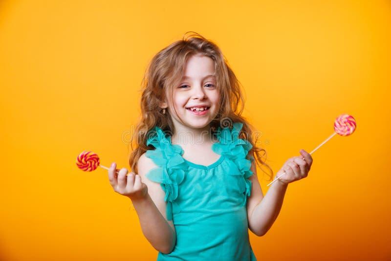 Criança engraçada com pirulito dos doces, menina feliz que come o pirulito grande do açúcar no fundo brilhante amarelo fotos de stock royalty free