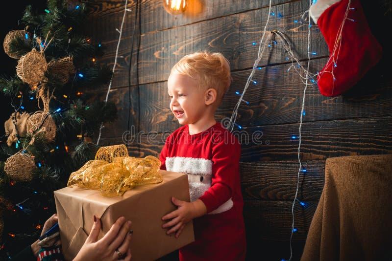 Criança engraçada de sorriso no chapéu de Santa que guarda o presente do Natal à disposição Bom Feliz Natal e ano novo feliz, um  imagens de stock royalty free