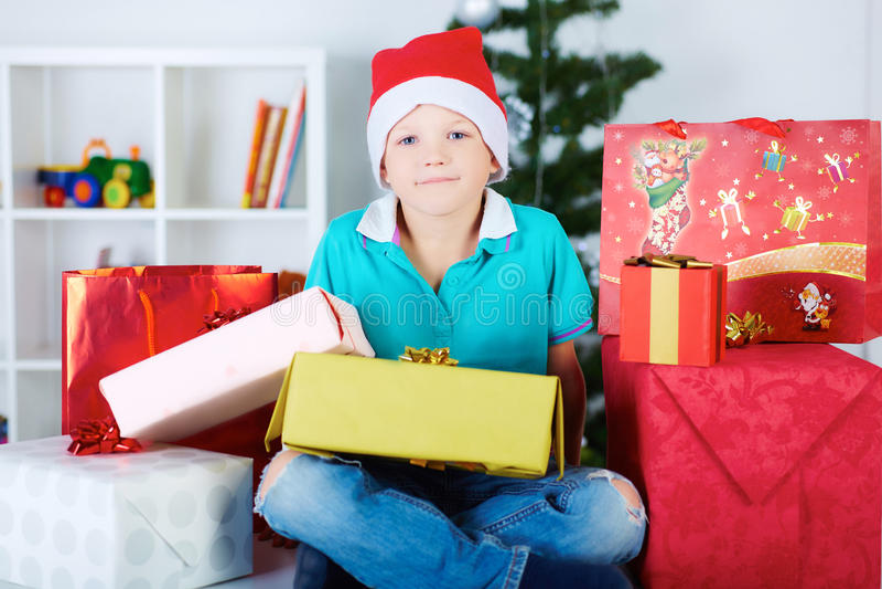 Criança engraçada de sorriso no chapéu vermelho de Santa com muitas caixas de presente imagem de stock