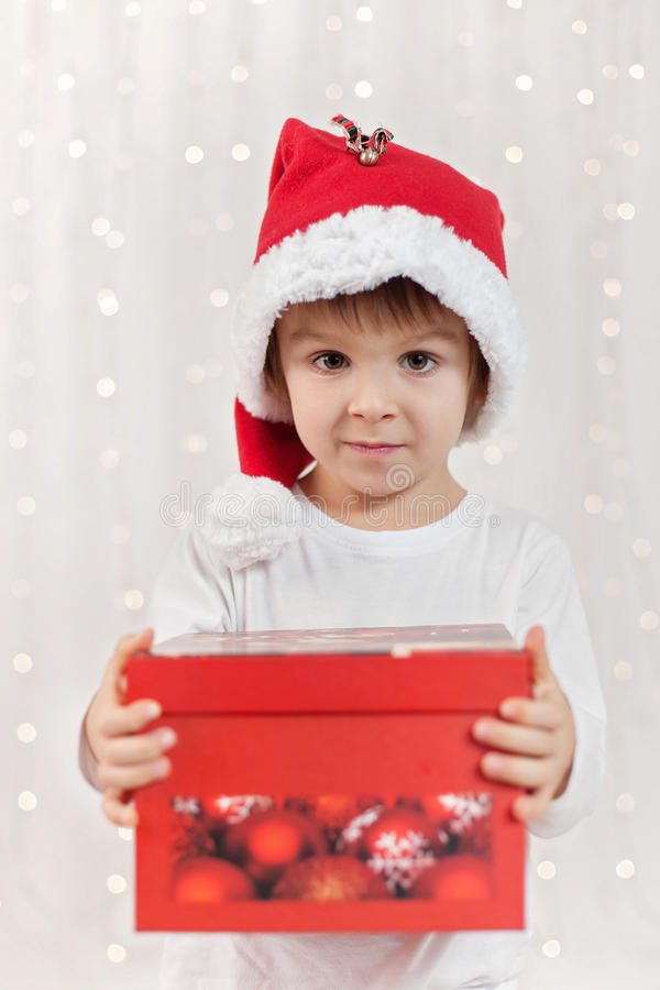 Criança engraçada de sorriso no chapéu vermelho de Santa que guarda o presente do Natal em h imagem de stock
