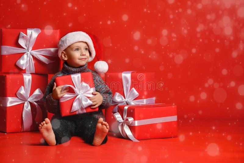 Criança engraçada de sorriso no chapéu vermelho de Santa que mantém o presente do Natal disponivel Conceito do Natal foto de stock